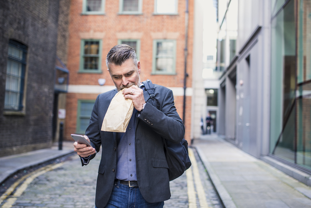 Man eating and working at the same time
